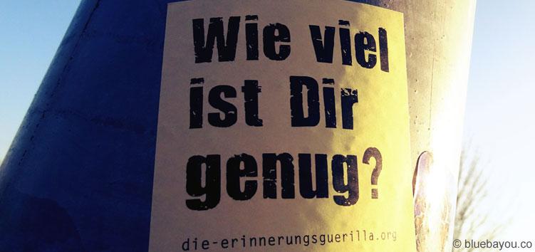 Wie viel ist Dir genug? Post-It der Erinnerungsguerilla an einer Laterne.