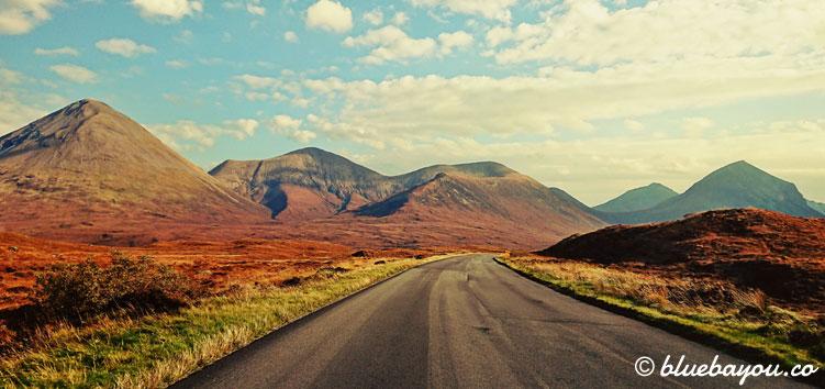 Fotoparade Roadtrip: Unterwegs auf Schottlands Straßen bei blauem Himmel und Sonne.