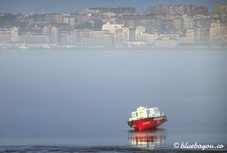Ein rotes Schiff in Spanien mit dem verschlafenen Santander im Hintergrund.