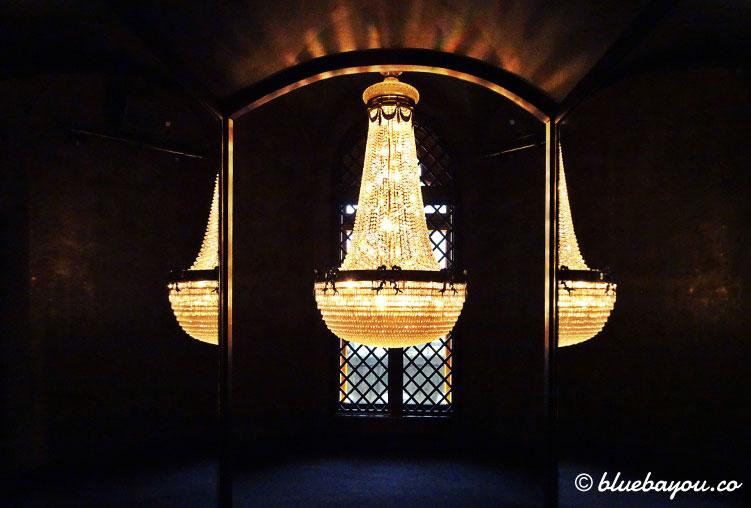 Fotoparade Licht: Ein Kronleuchter ist der einzige Gegenstand in einem kleinen Raum eines Bekleidungsgeschäfts in Hamburg.