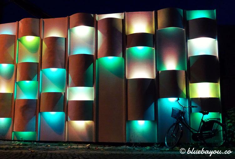 Fotoparade Stadtbild: Ein Fahrrad lehnt in Kopenhagen an einer beleuchteten Wand.