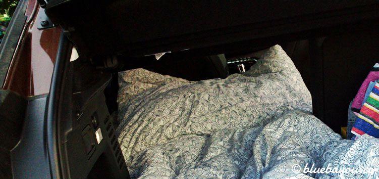 Im Auto schlafen: Rückbank teilweise umklappen und halb im Kofferraum schlafen.