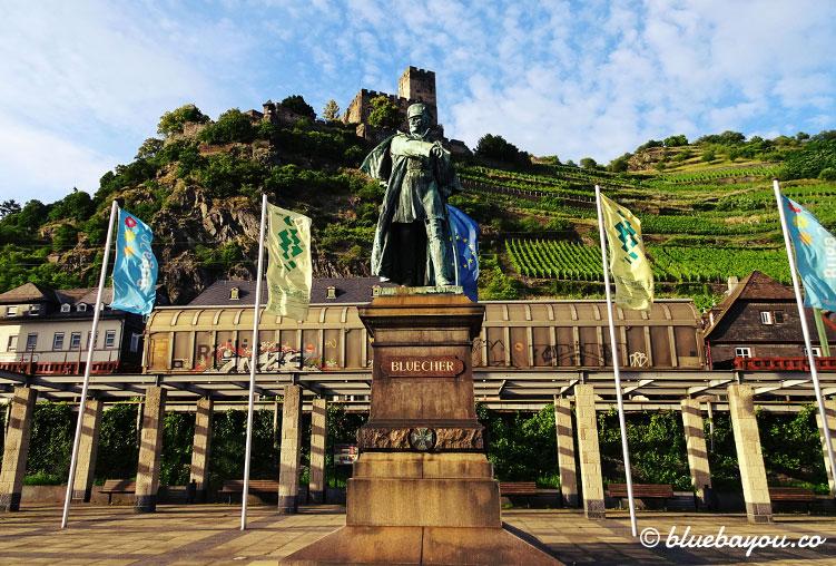 Blücher-Statue in Kaub vor einem Güterzug und der Burg Gutenfels.